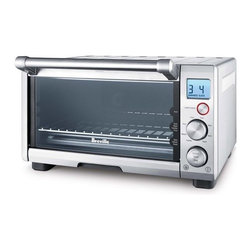"""Breville - Compact Smart Oven - Features: -Smart oven. -Material: Coated steel housing. -Non-stick interior and tempered glass door. -Function dial. -Temperature and time dial. -Temperature conversion button. -Frozen foods defrost button. -Backlit easy-read LCD. -Easy-clean, pull-out crumb tray. Specifications: -4 slice toast and 12"""" pizza capacity. -1800W Element IQTM. -10"""" x 10"""" Enamel baking pan. -10"""" x 10"""" Enamel broil rack. -Overall dimensions: 10"""" H x 16.5"""" W x 14.25"""" D."""