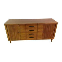 Pre-owned John Widdicomb Mid-Century Sideboard - This classic Widdicomb sideboard has brass handle pulls and feet with roll doors on each side, making it a lovely and reliable piece for any living room.     There is one largish chip on left side above door, which has been blended, but overall a great looking piece.