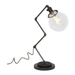 """Pre-owned Large Zig Brass Plumbing Table Lamp - Ball Shade - Shed light on any project with this vintage industrial inspired desk lamp. The lamps feature repurposed industrial plumbing pipe, brass hardware and a clear glass ball shade.     •  24"""" High x 12"""" Deep x 7"""" Diameter Base  •  1/8 IP Brass pipe  •  1/8 IP Repurposed industrial brass plumbing pipe fittings  •  Solid brass knob switch standard medium (E26) base socket  •  Solid brass 3 1/4"""" shade fitter  •  6"""" Diameter clear glass ball shade  •  8ft vintage style brown cloth covered twisted cord  •  Antique style brown Bakelite plug  •  110-250 Volts - 250 Watt max bulb (not included)  •  All UL Listed components  •  Vintage 2 ½ pound barbell  •  Reclaimed black honed marble base  •  Hand finished ebonized brass patina  •  Hand finished ebonized rust patina (barbell)  •  Handcrafted in Santa Barbara, CA by artisan Hilary Nagler"""
