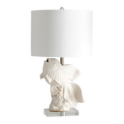 Kathy Kuo Home - Seaside Coastal Beach Contemporary Koi Fish Coral Beach Ceramic Lamp - A playful nautical motif takes center stage in this lovely,  blanc de chine style porcelain lamp.  Elevated by a small acrylic platform, the joyful fluidity of a koi fish in motion  is brought beautifully into the spotlight under a linen shade.  Alone or in a pair, it is a great way to mix a classic ceramic style into spaces influenced by European and Asian traditions.