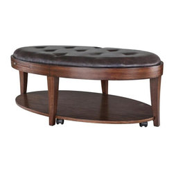 Magnussen Furniture - Oval Cocktail Table with Casters - Traditional style. Upholstered top with bottom shelf. Two pull out trays. Warranty: One year. Made from solid hardwood and PU. Chestnut finish. 51 in. W x 31 in. D x 19 in. H (79 lbs.). Care InstructionsThe beautiful chestnut finish applied to primavera veneers and select hardwoods on the Keaton Occasional Table Collection is only part of the story. Add a deep saddle brown eco-friendly PU and you have a cocktail table that does double duty as a comfy place to rest your tired feet. Add hidden casters and you have a bench that easily moves to the edge of the conversation area for additional seating. Not to be outdone, the end table and the demilune sofa table both have the same great transitional styling as the versatile cocktail table but with sparkly tempered glass. Make the Keaton Collection part of the story of your living areas!.