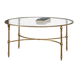 Uttermost Vitya Glass Coffee Table - A graceful, oval design in gold leafed, forged iron under sturdy, clear tempered glass. A graceful, oval design in gold leafed, forged iron under sturdy, clear tempered glass.