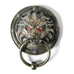 Grandin Road - Lion Door Knocker - Halloween Decorations and Decor - Classic lion's head doorknocker with light up eyes. Lion's eyes light up and glow red with each knock. Sculpted from all-weather resin with a metal ring. Aged-brass finish. Integrated keyhole hanger. This Halloween, make a fierce first impression with the Lion Door Knocker on your front door. With every knock of the metal ring, the lion's eyes light up and steadily glow red. The sculpted resin lion medallion and metal ring are finished in aged bronze, for the look of a classic doorknocker. This design is so splendid and sophisticated; you'll be tempted to leave it on your door all year long.  .  .  .  .  . Requires three watch-style batteries (included) . A Grandin Road exclusive.