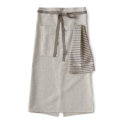 "Bambeco Linen Cafe Apron in Oatmeal - The Linen Cafe Apron in Oatmeal is as beautiful as it is useful. The eco-friendly linen/cotton blend is finished with sturdy grommets and ties in place with slate gray cotton twill. Inspired by men who love to cook and designed to fit both men and women, these aprons are long, extra wide for maximum coverage and just look good. Simple, but elegant, ideal for kitchen or table service and includes two deep pockets for holding tools or towels. These will quickly become your go-to apron; the fabric will just get softer and more luxurious feeling with use. Tea towel not included.  Dimensions: 33""L x 40""W  Care: Machine wash, tumble dry low"
