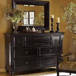 Tommy Bahama Home - Dresser w Mirror in Tamarind Finish - False Mirror:. Bordered with an egg-and-dart pattern. Deep tray design. Cast resin accents. Can be hung vertically or horizontally. 1.5 in. bevel. Overall: 36 in. W x 48 in. H (60 lbs.). Plate: 24.88 in. W x 36.88 in. HDresser: . Eight drawers. Top center drawer has drop-front pullout for media components. Vented back. Second center drawer has sliding felt jewelry tray. 68 in. W x 22 in. D x 44 in. H (280 lbs.). Made from mahogany solids, American maple and mahogany veneers. Special Care Instructions from Lexington FurnitureKingstown is a relaxed traditional collection inspired by British Colonial style, with a hint of Campaign and a touch of safari. The Tamarind finish is a rich aged black with rub-through to crimson and gold undertones beneath. The evocative designs provide a sense of a well-traveled life.of items hand selected during journeys around the globe.