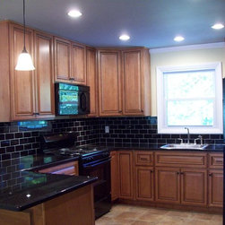 Marquis Cinnamon Kitchen Cabinets - Customer submitted photo of their completed kitchen in our Marquis Cinnamon Kitchen Cabinets.   The black appliances, countertop, and black tile backsplash really make the rope detailing and accents on the cabinets stand out.