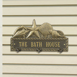 Frontgate - Personalized Shell Hook Plaque - Vintage Bronze/Verdigris or Bronze/Gold finish. Three hooks for hanging damp towels. Suitable for wet conditions, indoors or out. Christen a poolside patio or pool house with function and charm. Our Personalized Shell Hook Plaque offers ample space for a family name or location, topped by a collection of classic seashells. The rust-resistant cast aluminum has a powdercoat finish for all-weather durability.  .  .  . Made in USA.