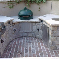 """Outdoor kitchen with natural stone - An outdoor kitchen grill area made with Greycastle Thin Veneer natural stone and 2 1/4"""" Natural Limestone tops.  Installation by Maverick Landscaping, stone provided by Sturgis Materials."""