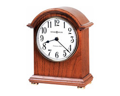 "Howard Miller - Howard Miller - Myra Mantel Clock - Travel towards classic sophistication with this magnificent model selection. Sleek clearly cast hands position themselves over the hour easily. Quality creation finds a home on any mantelpiece, nightstand, bedside in the name of neo classic contemporary. Golden knobs secure selection in place. * This arched mantel clock features a decorative top molding, a polished brass bezel, and turned, polished brass bun feet. . An off-white dial under convex glass features black Arabic numerals and black hands. . Finished in Oak Yorkshire on select hardwoods and veneers. . Automatic nighttime chime shut-off option. . Quartz movement plays Westminster chimes on the hour. . H. 8-3/4"" (22 cm). W. 7"" (18 cm). D. 3-1/4"" (8 cm)"