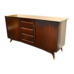 Pre-owned Vintage Walnut Console - A vintage, circa 1950s, Kent Coffey Mid-Century sideboard with brass tipped feet. The piece features refinished walnut. The console has a bifold door left and right: the left interior has 2 adjustable shelves and tray storage. The right interior has 1 adjustable shelf and one drawer on the bottom. The center section has 4 drawers.