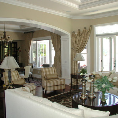 Custom Draperies - Photo of stationary side panels in Living Room mounted on decorative iron medallions and slanted to top of adjacent large window and then tied back. Stationary pleated side panels in Dining Room installed on large decorative wood pole and rings, then tied back to reveal the view.