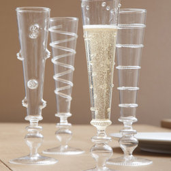 Verre Champagne Flute - Set of 4 - The Verre Champagne Flute is crystal-clear, easy to match with your dinnerware, but its personality is quirky and apparent in the designs applied to the blown glass.  Floral, dot, spiral, or ring designs texture the tapering outside of each handcrafted flute, making it pleasant to hold and balancing the bold flare and beaded edge of the stem and its wide foot below.