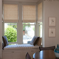 Motorized Roman Shades in a bay window and built in window seat - A custom built in window seat in a bay window does double duty as built in storage. Motorized roman shades make opening and closing easy.