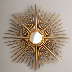 Golden Sunburst Mirror - A small round mirror resides inside the brilliant rays of this sunburst-framed mirror.