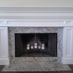 Collaborations with interior designers and architects - This transitional style fireplace mantle with columns is painted white with a semi-gloss sheen. It is a compilation of standard mouldings and custom mouldings that we milled on our flatbed CNC.