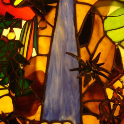 3D Stain Glass Jungle Picture in a Wall Light Box Frame - A blue draping glass was chosen for this waterfall.  It cascades over a cliff of boulders and splashes into foam of bubbles before running off in a green river.  A fern on the cliff face extends out from the picture with spindly thin green and yellow rippled glass.