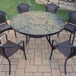 Oakland Living - 7-Pc Round Dining Set - Includes one table, six resin wicker dining chairs and metal hardware. Handcast. Traditional lattice pattern and scroll work. Fade, chip and crack resistant. Umbrella hole table top. Hardened powder coat. Warranty: One year limited. Made from rust free cast aluminum, steel and resin wicker. Black color. Minimal assembly required. Chair: 23.25 in. W x 25.5 in. D x 34 in. H (14 lbs.). Table: 60 in. Dia. x 29 in. H (70 lbs.). Overall weight: 180 lbs.This dining set is the prefect piece for any outdoor dinner setting. Just the right size for any backyard or patio. The Oakland Tuscany Collection combines southern style and modern designs giving you a rich addition to any outdoor setting.