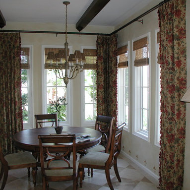 """Custom Draperies - Top tacked linen print draperies with tassel fringe installed over woven woods. Draperies are installed on 1 1/2"""" Antique Bronze iron poles with matching rings."""
