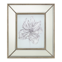 Silvery Blue Tulips IV Print with Mirrored Frame - Influenced by the luxurious botanical prints gracing the garden rooms of English country manses, the artwork presents a quiet blue background that introduces an intricate illustration of a magnificent bloom with curved petals and stem rendered in whispers of gray. The wide mirrored frame accented with petite beading in the bevel and each corner lends a touch of refined glamour to the Silvery Blue Tulips IV artwork.