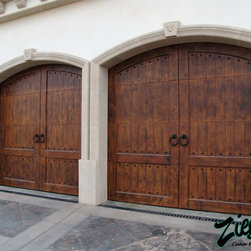 Mediterranean Style Garage Doors - The Mediterranean coast is perhaps one of the richest places in the world. Grand palaces and elegant villas over look the ocean and provide the perfect backdrop for our Mediterranean garage doors. Dark rich colors, dense hardwoods, and decorative iron hardware allow these doors to facade some of the most luxurious homes in the world.