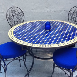 """Moroccan Outdoor - This beautiful blue and yellow 48"""" Moroccan mosaic table goes great with the four Bistro curly style, wrought iron chairs, and makes for a great outdoor dining set. These Moroccan tables that burst with color will compliment anyone's backyard."""