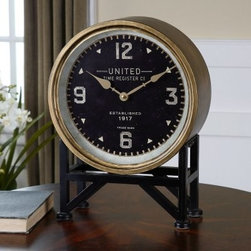 Uttermost Shyam Table Clock - 16H in. - The Uttermost Shyam Table Clock is a vintage-inspired piece deserving of prime real estate on your desk or table top. You can almost hear the train whistles and old-time radio programs when looking at the early 20th-century design. The Uttermost Shyam Table Clock achieves a delicate balance between industrious practicality and functional beauty with its iron, brass-finished body and aged black details. Its serious design is complemented with quartz movement; the most widely used timekeeping method worldwide. The large analog clock face features an aged 12, 3, 6, and 9, prominently stamped with geometric details in between.Place this piece among modern or traditional home decor; its timeless design fits right in for decades (or centuries?) to come.About UttermostThe mission of the Uttermost Company is simple: to make great home accessories at reasonable prices. This has been their objective since founding their family-owned business over 30 years ago. Uttermost manufactures mirrors, art, metal wall art, lamps, accessories, clocks, and lighting fixtures in its Rocky Mount, Virginia, factories. They provide quality furnishings throughout the world from their state-of-the-art distribution center located on the West Coast of the United States.