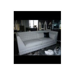 Inventory - This sofa is the love child of a rock star and glamor queen! It is upholstered in the finest white faux leather and finished with beautiful tufts on the back and arms. Rolled pillows and extremely soft seats make it extremely comfortable to sit on, while a shiny chrome trim adds some glamor to this sumptuous sofa. As with many of our items, it can be customized to make it truly unique and yours alone! 96 IN W 38 IN D 34 IN H