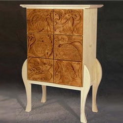 Chest of Morgan - This chest of drawers is made of solid Maple with hand carved Mahogany drawer fronts of Celtic animals. Each animal is unique yet they all flow into each other, as the legs curve up to embrace them. The drawer handles are carved into each drawer design. This chest is made from Maple, and Mahogany, with a polyurethane (maple), and oil varnish (mahogany).