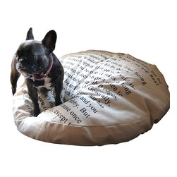 "Sugarboo Designs - Dog Bed - This plush, handmade dog bed is perfect for that special pooch in your life. Continue your casual, but beautiful decor style to include the items your pets love.  This canvas cover wraps around a plush down insert. The bed features a quote from the Velveteen Rabbit. Bed is 32"" in diameter.   Quote: ""You become. It takes a long time. That's why it doesn't happen often to people who break easily or have sharp edges or who have to be carefully kept. Generally, by the time you are Real, most of your hair has been loved off and your eyes drop out and you get loose in the joints and very shabby. But these things don't matter at all, because once you are Real you can't be ugly, except to people who don't understand.   About the Artist: Rebecca Puig is the artist behind Sugarboo Designs. Sugarboo is a family business that Rebecca and her husband, Rick, started in 2005. The name Sugarboo came from a couple of nicknames she has for her children, Jake and Sophie. They are the main inspiration for Sugarboo because Rebecca always wants to create products that remind us of the ones we love. As a little girl, Rebecca loved to paint and create things. She attended the University of Georgia graduating with a Studio Art degree. Rebecca is inspired by her family, nature, animals, old things, childrens' art and folk art. She also loves juxtaposing old and new, light and dark, serious subject matter with fluff and anything with a message. Rebecca believes in putting good out into the world whenever possible. Her hope is that each Sugarboo piece she creates will add a little good into the world.    Product Details:"