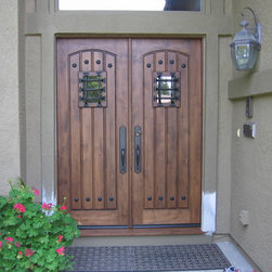 Doors - This pair of doors is made from Knotty Alder and features single v-grooved panels assembled as a pair.  This door features speakeasy ports with glass, allowing the occupants to view the person at the door. Large clavos and rustic hardware compliment the effect.