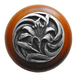"""Inviting Home - Tiger-Lily Cherry Wood Knob (antique pewter) - Tiger-Lily Cherry Wood Knob with hand-cast antique pewter insert; 1-1/2"""" diameter Product Specification: Made in the USA. Fine-art foundry hand-pours and hand finished hardware knobs and pulls using Old World methods. Lifetime guaranteed against flaws in craftsmanship. Exceptional clarity of details and depth of relief. All knobs and pulls are hand cast from solid fine pewter or solid bronze. The term antique refers to special methods of treating metal so there is contrast between relief and recessed areas. Knobs and Pulls are lacquered to protect the finish. Alternate finishes are available. Detailed Description: A very detailed and beautiful knobs are the Tiger Lily knobs. They are very delicate and bears a lot of positive history. The Tiger Lily is an orange flower that is covered in spots. It has been a useful medical remedy for many centuries. Its scent is said to suppress aggressive behavior and promotes overall good feeling. The smell is said as a superstition to give whoever smells it freckles."""