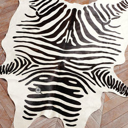 """Zebra"" Hide Rug - Hairhide rug with stenciled zebra stripes brings a touch of the wild to any room. Rug measures 5' x 7'."