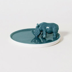 Thirsty Rhino Trinket Dish - Give your keys and spare change a lovely new home with this trinket dish. The striking image of the rhino drinking is enhanced by the gorgeous reflection it creates in the rich and natural blue glaze. Made of porcelain, this would look great on a side table in your hallway or living room.