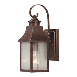 Elk Lighting - EL-47000/1 Town Square 1-Light Outdoor Sconce in Hazelnut Bronze - This tapering lantern is hung from a graceful curved arm and is accentuated by seedy glass panels. The hazelnut bronze finish intensifies the historic ambiance.