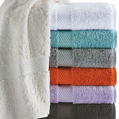 """Frontgate - Yves Delorme Etoile Guest Towel - Made of 83% Egyptian combed cotton, with 17% modal. Modal is a natural beechwood fiber that adds softness, durability and absorbency to cotton, and allows towels to dry faster. Choose from eight colors: Blanc, Nacre, Pierre, Lagon, Platine, Taupe, Orange and Parme. Loop length reduces snags. Advanced dye technique retains the strength and consistency of each color. Wrap yourself in a generous amount of luxurious modal terry. Loomed from premium, long-staple Egyptian cotton, our 700-gram Yves Delorme Etoile Guest Towels are deliciously soft, thick and absorbent, yet dry quickly thanks to a touch of modal. The towels are chicly finished with a woven band featuring a star (""""etoile"""" in French) pattern that continues throughout the collection.  .  .  .  .  . Generously oversized towels (with the exception of the American-sized bath towel) for a luxurious feel . A star design on the bath mat coordinates with a woven band on the towels . Machine wash with mild detergent and cold water; do not bleach; dry on low heat . Do not use fabric softeners or dryer sheets, which limit absorbency . To activate the towels' absorbency, use just one cup of white vinegar for the first few washes; this will remove the potato starch sizing needed to weave the towel . Designed in France, made in Turkey."""