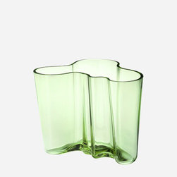 "iittala - Alvar Aalto Large Apple Green Vase - A shape constantly interpreted, the Alvar Aalto collection of vases stays true to the original design concept. More than 70 years after the original debut, the design continues to provoke attention by letting the owner decide its use and complementing our busy lives with a touch of nature. Filled with fresh cut flowers or arranged with other collection pieces as works of art, this eternal classic is essential to the modern home. The Aalto glass pieces have a multi-stage production. The non-leaded crystal is first mouth blown before going into a wooden mold to create the classic Aalto shape. The pieces are then hand cut and go through several polishing and finishing steps before they are completed, creating a piece worthy of permanent display at the Museum of Modern Art. In addition to the standard Aalto colors, each year iittala selects two new glass colors to run in limited production. Features: -Mouth blown non-leaded crystal -Features designer's signature on the bottom -Not dishwasher safe, hand wash only -Overall dimensions: 6.25"" H"