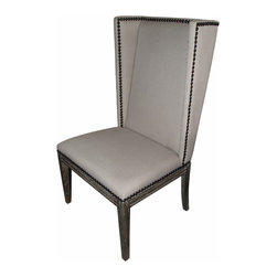 Nailhead Dining Chair - Armless - Angular, sleek, and versatile, this linen-upholstered dining chair or occasional chair has an unusual shape inspired by the traditional wingback, but armless for ease at the table. Dark nailhead trim outlines the simple geometric shapes of the high back and deep seat. Below, tall cerused oak legs support the chair; the rear pair curves slightly outward, bringing a note of elegant style to the rustic look of the dining chair. To bring a more eclectic look to your dining space, mix this chair with the more traditional armed version.