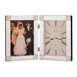 Bulova - Cermonial Picture Frame Clock - This Ceremonial picture frame clock features a hinged metal case with a chrome finish.  It has a 5 x 7 photograph opening and a protective glass lens.  A 3.25 x .75 engraving plate is included.  It requires one AA battery, which is not included. Bulova - B1254