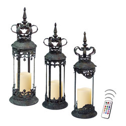 """Asian Import + USA - Monaco Lantern Set with Flameless Wax Color Candles - Beautifully crafted antique finished cylinder lanterns are perfect for highlighting pillar candles or as decorative containers. Each is 16"""" tall with clear glass cylinders and removable ornate crown covers. Display these royal inspired lanterns in a special place for an elegant accent. Included are three 4"""" Avion Select melted edge wax color candles with remote control timer. Note that candles pictured are for presentation only. The candles included in the set are described above. Set of 3"""