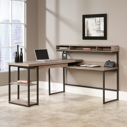 Sauder - Sauder Transit L-Shaped Desk - Salt Oak Multicolor - 414417 - Shop for Desks from Hayneedle.com! The Sauder Transit L-Shaped Desk Salt Oak does more with less thanks to a streamlined space-efficient design that offers plenty of storage and multi-purpose work space. Crafted from steel and high-density particleboard with a salt oak finish this modern computer desk is suitable for the studio office or home office.About SauderSauder is North America's leading producer of ready-to-assemble (RTA) furniture and the nation's fifth largest residential furniture manufacturer. Based in Archbold Ohio Sauder also sources furniture from a network of quality global partners including a line of office chairs that complement its residential and light commercial office furniture. Sauder markets more than 30 distinct furniture collections in a full line of RTA furnishings for the home entertainment home office bedroom kitchen and storage.Sauder is a privately held third-generation family-run business. The company prides itself on its awareness that all function and no fashion makes for a dull living space when it comes to home furnishing products. That's why Sauder's award-winning design team has produced more than 25 collections of stylish furniture that span the design spectrum. From minimalist modern or contemporary to classic 18th century or country styles Sauder has what you're looking for. The company offers more than 500 items - most priced below $500 - that have won national design awards and generated thousands of letters of gratitude from satisfied consumers.