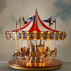 Horchow - Anniversary Carousel - A true collector's piece, this oversized carousel features a classic peaked fabric roof and a wooden base and is festooned with flags that move up and down with the hand-painted animals. Illuminated facade panels. Musical light show with hundreds of....