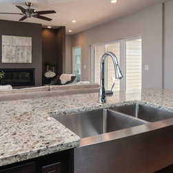6513 Hitching Post - Kitchen island with stainless apron front farmhouse sink and Crema Pearl Granite countertops.