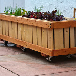 """M28, 2 x 7.5' x 25"""" Mobile Planter - Developed to allow people to grow healthy organic produce at home and provide a means to partially reduce our carbon foot print. Each planter allows plants to easily follow the sun and allow flat hardscapes to be used for multiple purposes. Taller planters are offered for those with chronic back problems or other physical limitations and handicaps (up to 42"""" tall). The planters are sturdy and built to last. Each planter is designed to last over twenty years plus. Construction is super sturdy. Made of hand selected Western timber (50% western red cedar / 50% plant oil and mineral and plant oil cured Douglas Fir. All wood FSC or SFI certified. Some wood is from recycled sources.). Planters are able to withstand frequent movement while supporting the weight of deep rich loamy soil. The boxes have an absence of shoddy staples, nails, pegs and rods. Most hardware is marine quality epoxy coated caseharden steel (Last longer- stronger than stainless steel). Lined with welded three-ply non-PVC pond liner. Planter bottoms are plumbed with drains that allow water to be diverted or conserved (re-used). Most materials, more than 90% of our materials are insourced from places like: Alabama, California, Illinois, Massachusetts, Ohio, Pennsylvania and South Dakota. Planters are designed, fully assembled and tested in Ventura, California. Planters can be shipped almost anywhere fully or near fully assembled (wheel chassis might have to be removed for some shipping carriers). Photo by Kurt Preissler"""