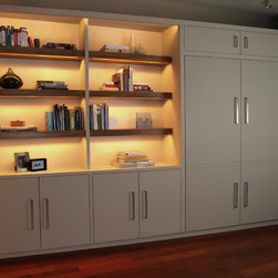 BOOKSHELF WITH MURPHY BED - A custom-designed open cabinet, with walnut floating shelves, concealed lighting, and a compartment that conceals a murphy-bed.