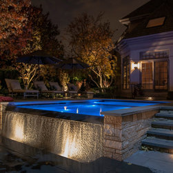 2013 - ILCA Gold Award for Residential Construction - The lower terrace exposes the infinity edge of the spa. Accent lighting highlights the playful nature of the textured waterwall behind.