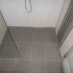 Modern Tiles Shower with Quick Drain - This shower illustrates the versatility of ProLine drains - they can be places so you barely notice them. This linear drain is positioned against an interior wall in this barrier-free shower. This allows the uninterrupted tilework to shine through. Our recommendation is to locate the drain where people are not going to stand on it, where it require the least amount of work and be as much out of sight as possible.
