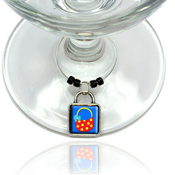 """Made on Terra - Purse Bag Handbag Shopping Polka Dot Wine Glass Silver Charm - Your guests have arrived and the atmosphere is electric. A sip of wine here, a sip of a cocktail there and you find the conversation turning to the charming baubles you've placed on the glasses, something special you chose for each of your eclectic guests. They love them and appreciate your thoughtfulness. You love them for their uniqueness and that no one forgets which glass they were using.  Choose from Made on Terra's many designs for the best party ever. Ring is 1"""" diameter; measures 2"""" from top of ring to bottom of charm. Made of metal and plastic. Sold individually."""