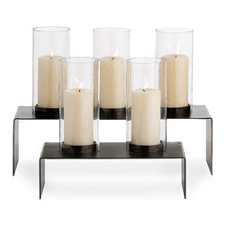 Hall Candle Holder - Set of 2 - Their simple design is contemporary; their coloration, classic. The Hall Candle Holder presents an iron angled platform in a rich blackened finish. Atop the platform are sleek cylinders of clear glass that house three-inch pillar candles. Available as a set of two, the holders may be used together for a stepped look or displayed as singles along a sideboard, fireplace mantle, or as a dining table centerpiece.