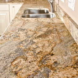 Yellow River Granite - Yellow River Granite is a subtle, but complex stone with a lilting pattern of gold, brown, caramel, black, white, and cream over a gray background. It is quarried in Brazil. It varies a good deal from slab to slab so make sure you pick out the particular slab for your project.