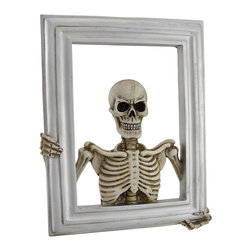 Zeckos - Skeleton Picture Frame Wall Mount or Tabletop Display - This skeleton picture frame is a great Halloween prop, and it will makes guests do a double take when displayed with your family photos Made of cold cast resin, it measures 9 1/4 inches tall, 7 3/4 inches wide, and 1 inch deep. This piece can be displayed on mantels, tables, and shelves, and it also has a hanger on the back so you can hang it on the wall. It makes a great gift for collectors of macabre art, and is sure to be admired.